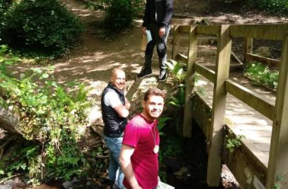 3 men taking part in a scavenger hunt by a bridge